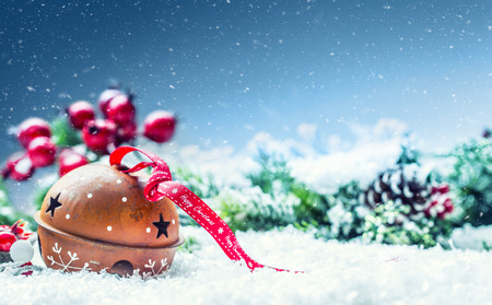 Christmas balls jingle bells. Red  ribbon with text Happy Christmas. Snowy abstract background and decoration. Stock Photo
