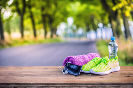 Pair of yellow green sport shoes towel water smart pone and headphones on wooden board. In the background forest or park trail.Accessories for running sport. Archivio Fotografico