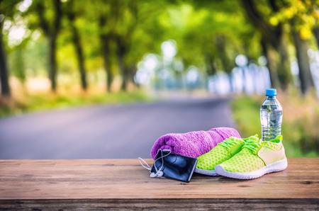 Paire de vert jaune chaussures de sport d'eau serviette pone et casque à puce sur planche de bois. Dans la forêt de fond ou parc trail.Accessories pour l'exécution de sport. Banque d'images - 63364940
