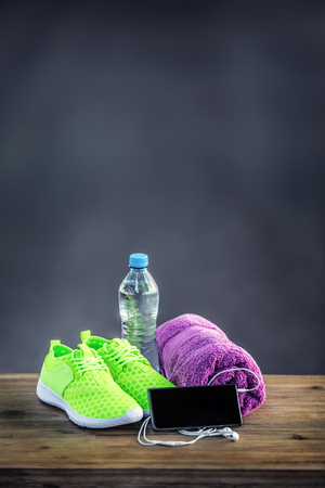 pone: Pair of yellow green sport shoes towel water smart pone and headphones on wooden board. In the background forest or park trail.Accessories for running sport. Stock Photo
