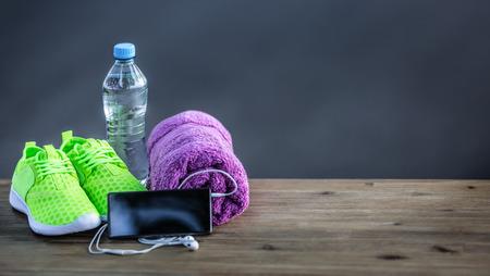Paire de vert jaune chaussures de sport d'eau serviette pone et casque à puce sur planche de bois. Dans la forêt de fond ou parc trail.Accessories pour l'exécution de sport. Banque d'images - 63364947
