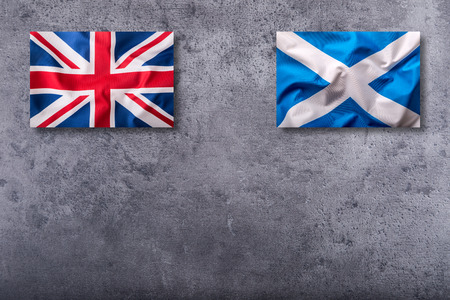 england politics: Flags of the united kingdom and scotland on concrete background. Stock Photo