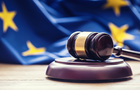 Judges wooden gavel with EU flag in the background. Symbol for jurisdiction. Фото со стока