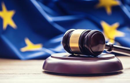 Sędziowie drewniany młotek z flagą UE w tle. Symbol jurysdykcji.