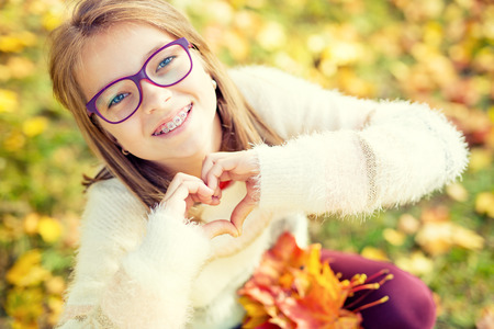 cute braces: Smiling little girl with braces and glasses showing heart with hands.Autum time.