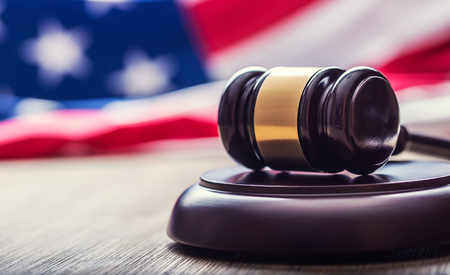 jurisdiction: Judges wooden gavel with USA flag in the background. Symbol for jurisdiction.