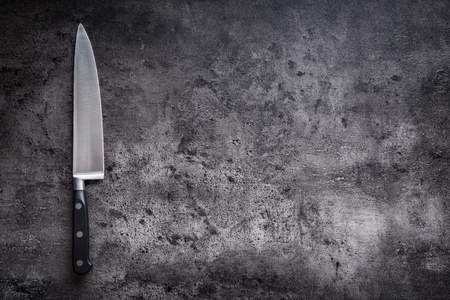 Kitchen knife on concrete or wooden board. Banque d'images