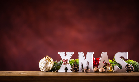 Christmas. Xmas word made of wooden letters on a wooden board table. Christmas balls pine cone star fir twig as decoration. Stock Photo