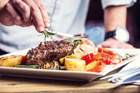 Chef en la cocina del hotel o restaurante cocinando solo las manos. Filete de ternera preparado con decoración vegetal.