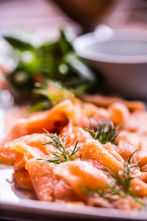 Salmon. Sliced smoked salmon with dressing and herb decoration.Serving sliced salmon in a restaurant or hotel. Stock Photo