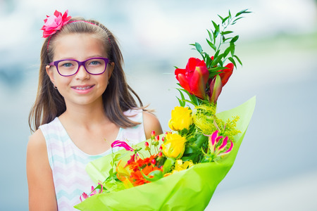 gifting: Beautiful little girl posing with a large bouquet of flowers. Girl with braces and glasses.