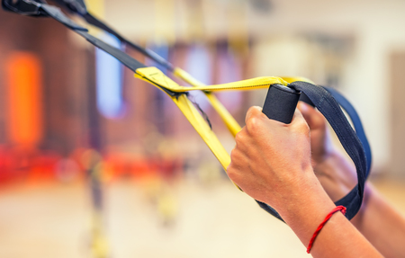 TRX. Female hands with fitness TRX straps in gym. Banco de Imagens