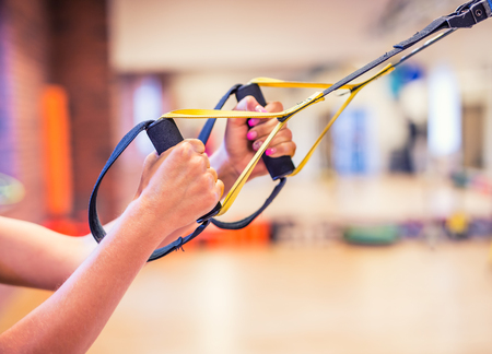 TRX. Female hands with fitness TRX straps in gym. Stock Photo