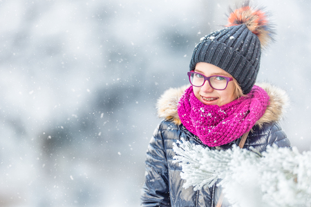 Beauty Winter Girl Blowing Snow in frosty winter park or outdoors. Girl and winter cold weather.
