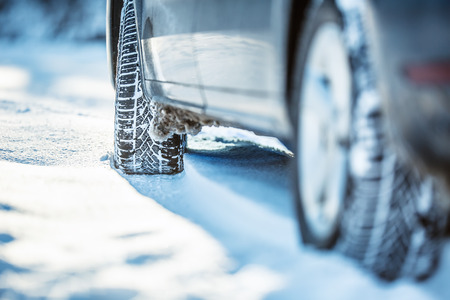 traction: Closeup of car tires on a snowy road.Blizzard on the road. Stock Photo