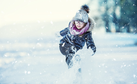Young girl are playing with snow.Beauty Winter happy Girl Blowing Snow in frosty winter park or outdoors. Girl and winter cold weather.