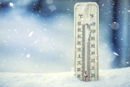 Thermometer on snow shows low temperatures under zero. Low temperatures in degrees Celsius and fahrenheit. Cold winter weather twenty under zero. Banco de Imagens