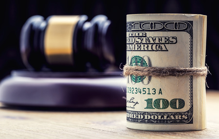 Judges hammer gavel. Justice dollars banknotes and usa flag in the background. Court gavel and rolled banknotes. Still life of a bribery, corruption in the US judicial system. Stock Photo