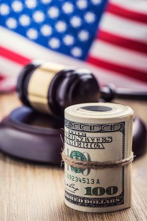 bribery: Judges hammer gavel. Justice dollars banknotes and usa flag in the background. Court gavel and rolled banknotes. Still life of a bribery, corruption in the US judicial system. Stock Photo