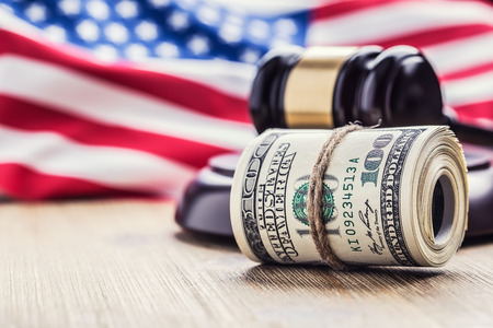 Judges hammer gavel. Justice dollars banknotes and usa flag in the background. Court gavel and rolled banknotes. Still life of a bribery, corruption in the US judicial system. Banco de Imagens
