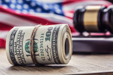 auction win: Judges hammer gavel. Justice dollars banknotes and usa flag in the background. Court gavel and rolled banknotes. Still life of a bribery, corruption in the US judicial system. Stock Photo