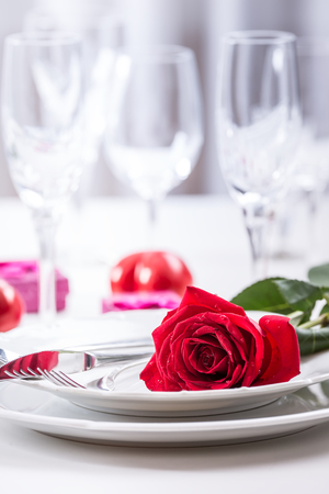 Table setting for valentines or wedding day with red roses. Romantic table setting for two with roses plates cups and cutlery. Banco de Imagens