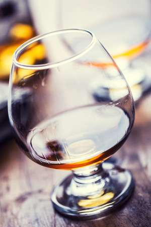 Glass whiskey cognac brandy or rum.One half full glasses of cognac on a wooden surface. Stock Photo