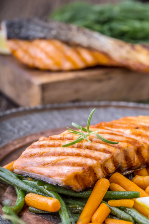 Salmon fillets. Grilled salmon, sesame seeds herb decoration on vintage pan or black slate board. fish roasted on an old wooden table.Studio shot. Stock Photo