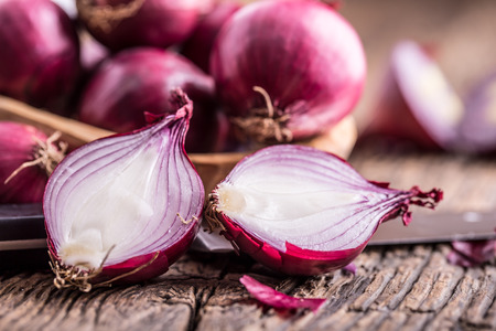 red onions: Onion. Red onions on very old oak wood board. Selective focus.