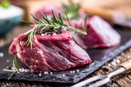 Raw beef meat. Raw beef tenderloin steak on a cutting board with rosemary pepper salt in other positions.