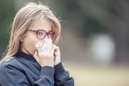 Girl with allergy symptom blowing nose. Teen girl using a tissue in a park.
