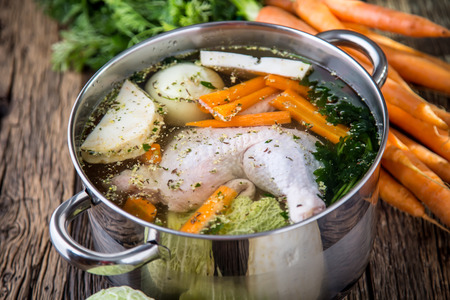 Top view of chicken soup on wooden table with vegetable. Banco de Imagens