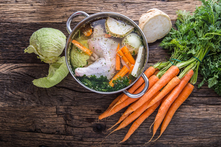 Top view of chicken soup on wooden table with vegetable. Banque d'images