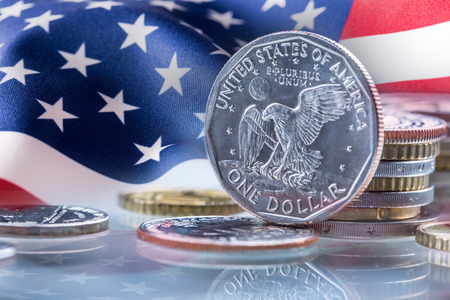 Dollar coins and USA flag in the background. USA Dollar coins standing on edge supported on coins Stock Photo - 73445051
