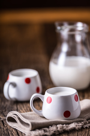 Milk. Cove or goat milk. Pouring milk into glass. Reklamní fotografie