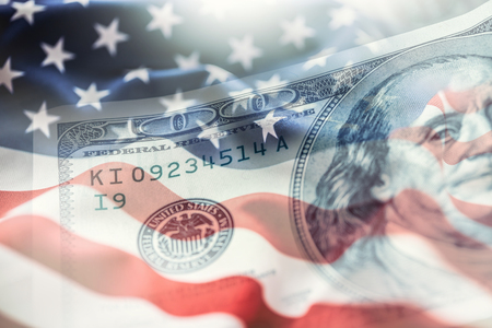 USA flag and American dollars. American flag blowing in the  wind and 100 dollars banknotes in the background. Archivio Fotografico