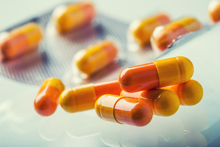 Pills Tablets Capsule or Medicament freely laid on glass background.