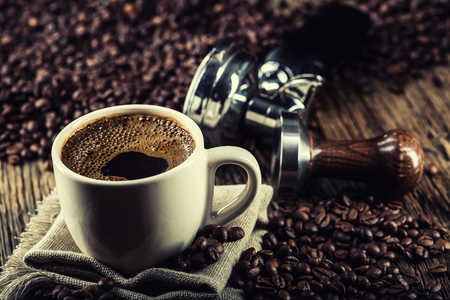 Coffee. Cup of black coffe with coffee beans tamper and portafilter. Stock Photo