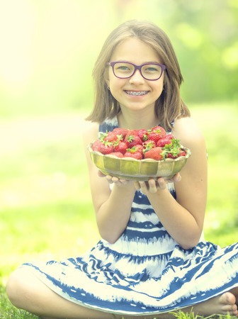 Petite petite amie avec un bol plein de fraises fraîches. Pré-adolescente avec des lunettes et des dents - accolades dentaires.