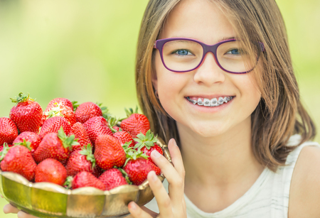 Cute little girl with bowl full of fresh strawberries.  Pre - teen girl with glasses and teeth - dental  braces.