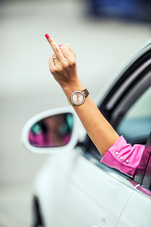 rudeness: Attractive woman shows obscene gesture from a car. Stock Photo