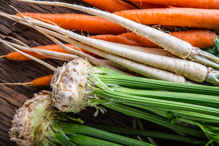 Carrot parsnip celery. Celery carrot and parsnip on rustic oak table Stock Photo