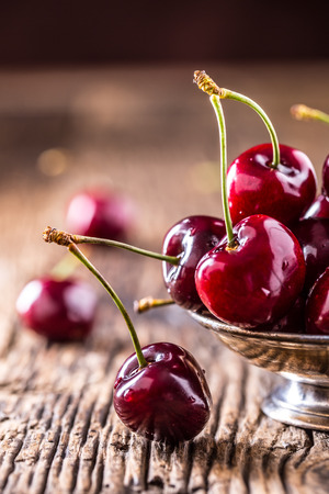 background: Cherries. Fresh sweet cherries. Delicious cherries with water drops in retro bowl on old oak table.