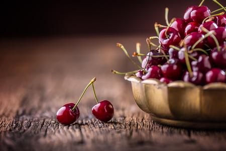 Cherries. Fresh sweet cherries. Delicious cherries with water drops in retro bowl on old oak table.