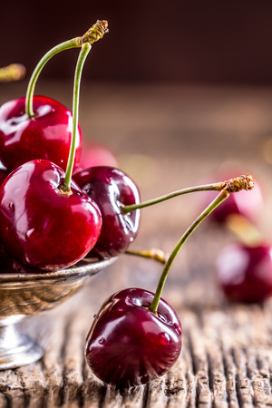 Cherries. Fresh sweet cherries. Delicious cherries with water drops in retro bowl on old oak table.