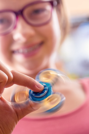 roller: Fidget Spinner. Cute young girl playing with fidget spinner.