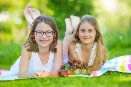 Two cute sisters or friends in a picnic garden lie on a deck and eat freshly picked cherries. Banque d'images