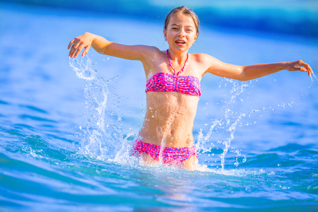 Cute young girl playing in the sea.  Happy pre-teen girl enjoys summer water and holidays in holiday destinations.