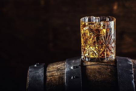 위스키 음료. 오래 된 목조 배럴에 위스키의 유리입니다.