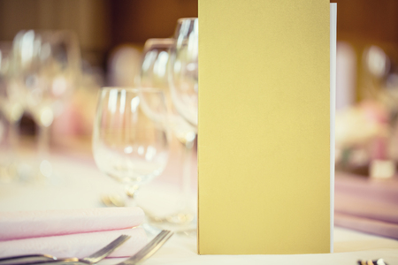 wedding table setting: Served table with menu brochure in restaurant, closeup. Free space for your text or information.